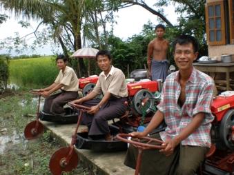 支援によって提供されたトラクターにまたがり、笑顔の村人たち