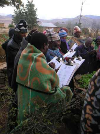 菜園を取り囲んで、モニタリングの方法を学ぶ村人