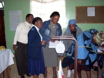 研修で子どもの体重を測定するための器具の使い方を学ぶコミュニティ・ヘルス・ワーカーたち